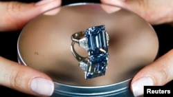 A Christie's employee poses with the 14.62 carats Oppenheimer Blue diamond during a preview in Geneva, Switzerland May 12, 2016.
