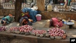 Indian vendors selling onions rest on a sidewalk under the shade of a tree on a hot summer day in Hyderabad, India, Monday, May 25, 2015.