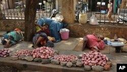 دست فروش های هندی در سرک پیاده رو زیر سایۀ درخت خوابیده اند