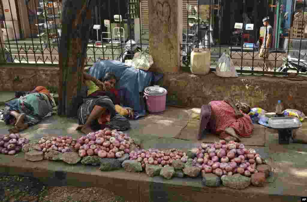 Para penjual di India beristirahat di bawah pohon di tengah gelombang panas, di Hyderabad (25/5). (AP/Mahesh Kumar A.)