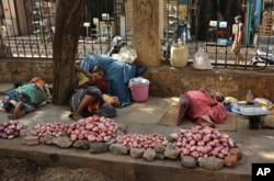 Indian vendors selling onions rest on a sidewalk under the shade of a tree on a hot summer day in Hyderabad, India.
