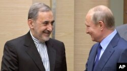 Russian President Vladimir Putin, right, shakes hands with Ali Akbar Velayati, a senior adviser to Iran's Supreme Leader Ayatollah Ali Khamenei, at Novo-Ograyovo outside in Moscow, Russia, Thursday, July 12, 2018.