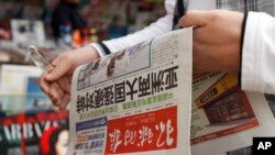 FILE - A Chinese man holds a copy of Global Times newspaper in this 2010 photo.
