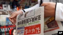一个中国人拿着《环球时报》,2010年。(资料图)