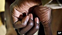 A prospective Sudanese voter dips his finger in ink at a voter registration facility in Glendale, Arizona, 26 Nov. 2010