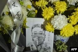 摆放在武汉市中心医院后湖院区的李文亮医生遗像和供鲜花。(2020年2月7日)