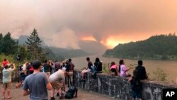 People at a viewpoint overlooking the Columbia River watching the Eagle Creek wildfire burning in the Columbia River Gorge east of Portland, Ore., Sept. 4, 2017.