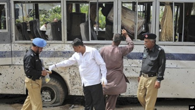 Security officials collect evidence at the site of a bomb blast in Karachi, April 28, 2011.
