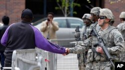 Warga setempat bersalaman dengan anggota pasukan garda nasional AS di balai kota Baltimore, Maryland (1/5). Pasukan garda nasional telah ditarik mundur dari Baltimore.