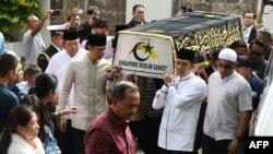 Mantan presiden RI Susilo Bambang Yudhoyono (kiri) berjalan di samping peti jenazah istrinya, Ibu Ani Yudhoyono, yang wafat di Singapura, Sabtu, 1 Juni 2019. (Foto: Roslan Rahman/AFP)