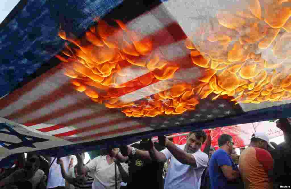 Người biểu tình Li-băng và Palestine đốt cờ Mỹ và Israel trong một cuộc biểu tình lên án các cuộc không kích của Israel vào Dải Gaza, ở thành phố cảng Sidon phía nam Li-băng.