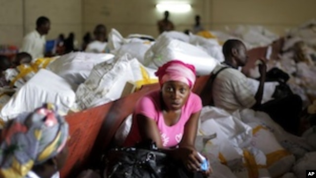 Election volunteers sit on bags containing ballots as they wait for tally sheets to be computed at the Fikin compilation center in Kinshasa, Democratic Republic of Congo, Thursday, Dec. 1, 2011.