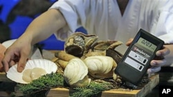 Imported seafood from Japan is screened for radiation by a chef at a Japanese restaurant in Hong Kong to make sure the food is safe to eat, March 22, 2011