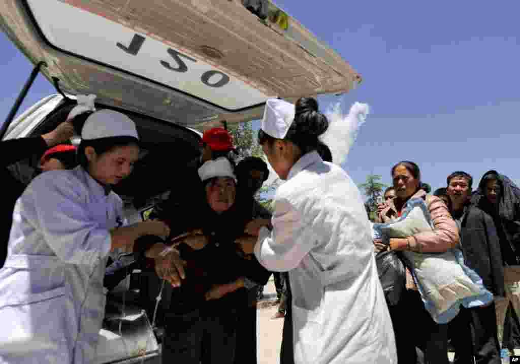 Seorang perempuan korban terluka dalam gempa ditolong oleh pekerja medis di daerah Minxian, provinsi Gansu, China (22/7).