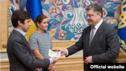 President Petro Poroshenko (R) hands a Ukrainian passport to Vladimir Fedorin as Maria Gaidar looks on, at a ceremony in Kyiv, Ukraine, August 4, 2015. (Photo source - president.gov.ua)