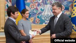 President Petro Poroshenko (R) hands a Ukrainian passport to Vladimir Fedorin as Maria Gaidar looks on, at a ceremony in Kyiv, Ukraine, August 4, 2015. (Photo source - president.gov.ua)