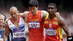 China's Liu Xiang is helped from the track by Britain's Andrew Turner, left, and Spain's Jackson Quinonez after falling in a men's 110-meter hurdles heat at the 2012 Summer Olympics, London, Aug. 7, 2012.