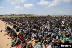 Palestinians attend Friday prayer during a tent city protest along the Israel border with Gaza, demanding the right to return to their homeland, in the southern Gaza Strip, March 30, 2018.