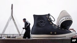"""Classic """"Chuck Taylor"""" sneakers are positioned outside the world headquarters of Converse, Inc. as a runner passes in Boston, Dec. 29, 2016."""