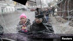 22일 우크라이나 도네츠크의 버스 사고 현장에서 사람들이 포격을 맞은 버스 안을 들여다보고 있다.