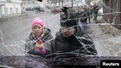Người dân nhìn qua tấm kính trước bị vỡ của chiếc xe buýt điện trúng đạn pháo ở Donetsk hôm 22/1.