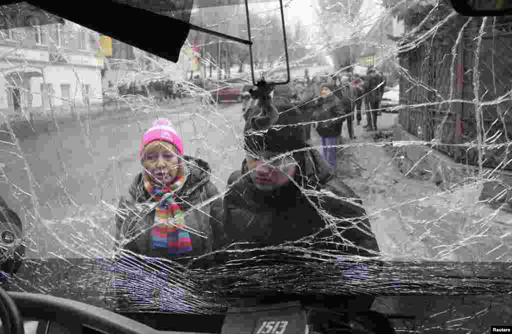 People look through the front windshield of a damaged trolleybus in Donetsk. At least six civilians were killed when a shell or a mortar hit a trolleybus stop in the rebel-controlled city in eastern Ukraine, a witness said.
