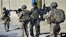 Lance Cpl. Juan Delacerda, of Kerrville, Texas, right, and Lance Cpl. Adam Rader, of Lodi, California, with India company, 3rd Battalion 5th Marines, First Marine Division, accompanied by an Afghan soldier patrol in Sangin, Afghanistan, Nov 11, 2010 (file