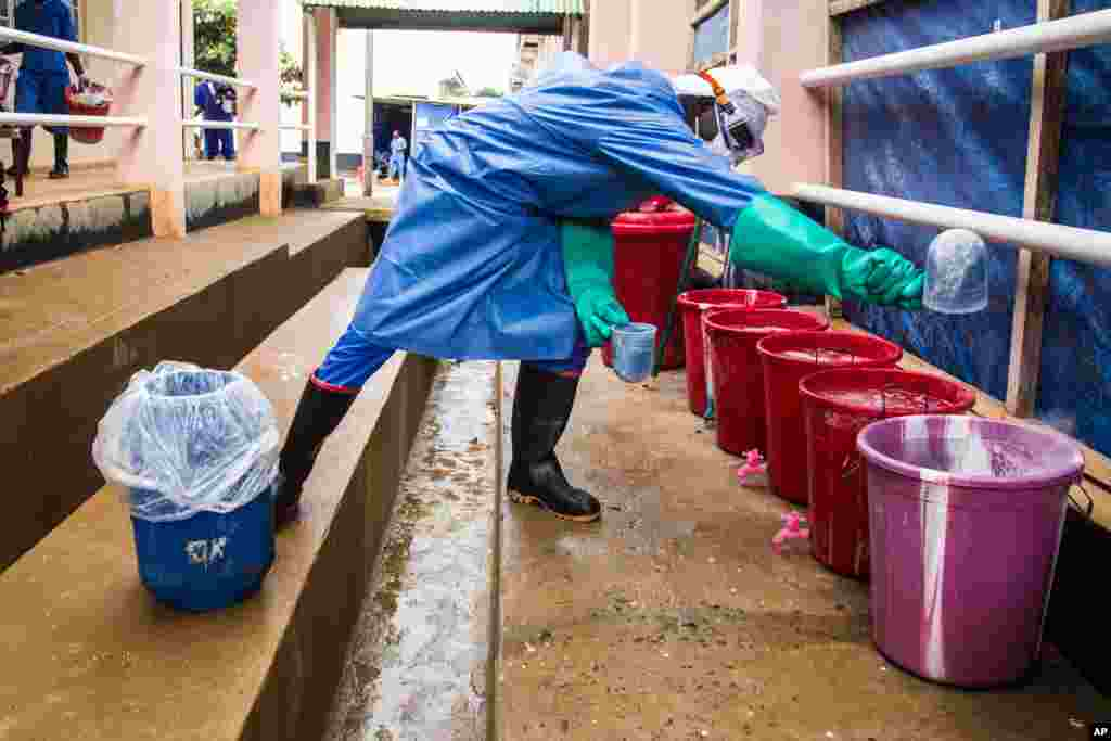 A healthcare worker mixes chlorine with water at an Ebola treatment center in Hastings, Freetown, Sierra Leone, Oct. 15, 2014.