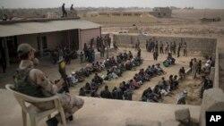 1일 이슬람 수니파 무장단체 ISIL 점령지에서 탈출한 주민들이 모술 남부 슈와이라흐의 회당 밖에 군인들의 감시를 받으며 모여있다.