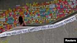 一位女士在香港一处过街天桥阅读民主抗议者留下的字条。