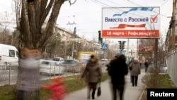 "People walk under a poster that reads, ""Together with Russia. March 16 - referendum"", in the centre of Simferopol, March 12, 2014."