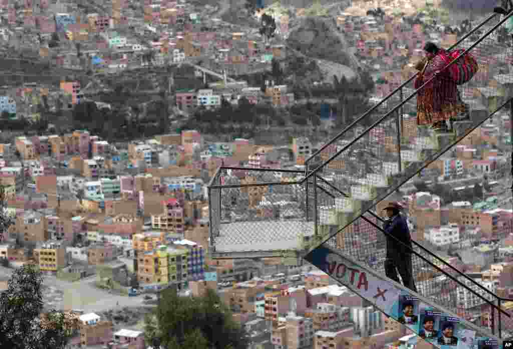 A man and a woman walk through the stairs of an overpass decorated with posters of Bolivia's President Evo Morales in La Paz, Bolivia, Oct. 9, 2014. Bolivia will hold general elections on Sunday.