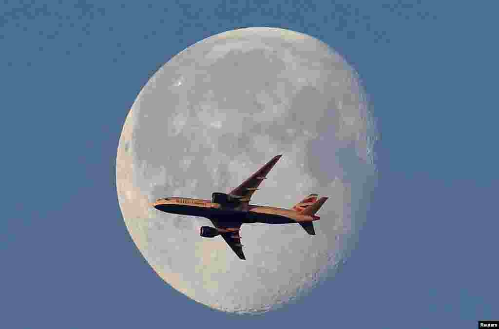 A British Airways passenger plane flies in front of the moon above London.