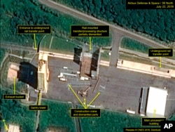 FILE - This July 22, 2018, satellite image released and annotated by 38 North on Monday, July 23, shows what the U.S. research group says is the partial dismantling of the rail-mounted transfer structure, at center, at the Sohae launch site in North Korea.