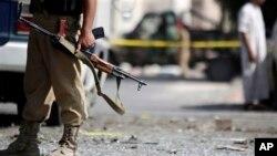 一名也门士兵2013年9月9号守卫在萨那巴士受到炸弹袭击的现场。