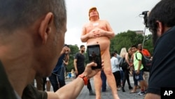 People take photos of a statue of a naked Republican presidential nominee Donald Trump in New York's Union Square, Aug. 18, 2016. City parks workers later removed the statue.
