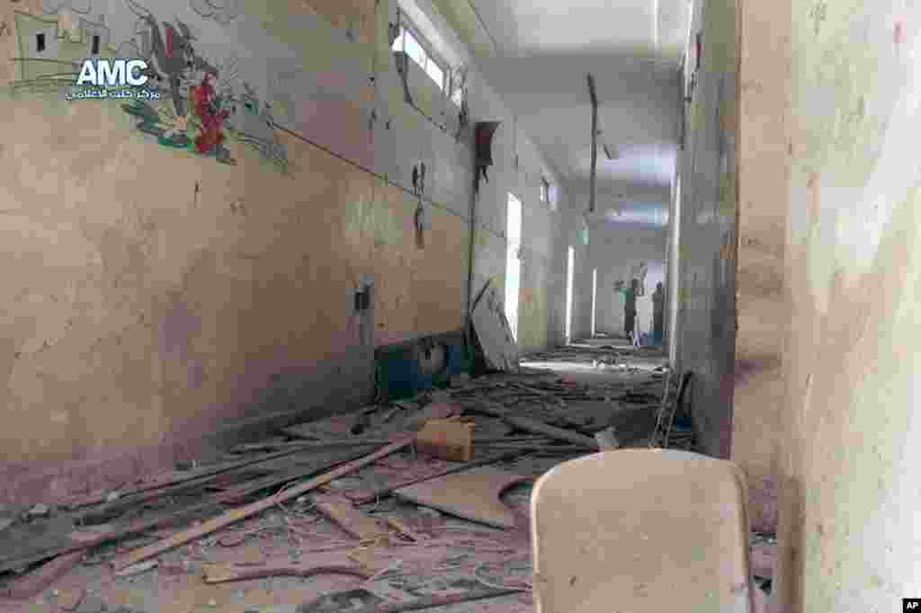 This photo provided by the anti-government activist group Aleppo Media Center shows two Syrian men standing inside a school that was hit by a Syrian government air strike in Aleppo, April. 30, 2014.