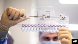 Seorang teknisi memeriksa botol berisi vaksin COVID-19 Pfizer-BioNTech di fasilitas perusahaan di Puurs, Belgia, Maret 2021. (Pfizer via AP)