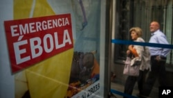 People walk by an advertising calling for financial help to fight Ebola in Africa in Madrid, Spain, Oct. 7, 2014.