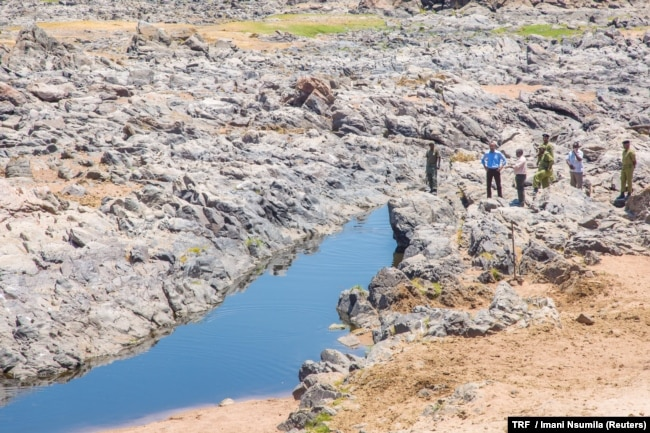 FILE - January Makamba, Tanzanian Minister of State for the Environment, and other officials inspect the dwindling water of the Ruaha river, in Kilolo district, Tanzania, Oct. 19, 2016.