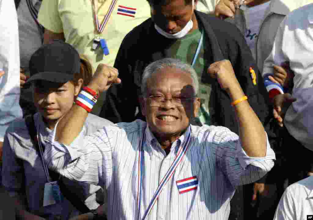 Thai anti-government protest leader Suthep Thaugsuban holds clenched fists during a march with his supporters in Bangkok, Thailand, Dec. 22, 2013.
