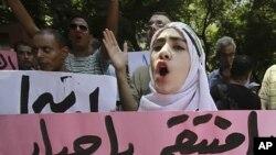 """이집트 카이로에서 시리아의 반정부 시위를 지지하기 위해 열린 집회에서 참가자들이 """"신이시여, 복수를!"""" 이라는 구호가 적혀 포스터를 들고 구호를 외치고 있다."""