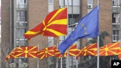 FILE - Macedonian and European flags fly side by side in Macedonia's capital Skopje, March 15, 2012.