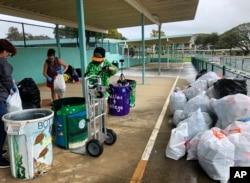 """Genshu Price (kanan) dan relawan lainnya di S.W. King Intermediate School di Kāne'ohe, Hawaii, menyortir kaleng dan botol untuk """"Bottles4College"""", 18 Maret 2021. (Foto: Maria Price/Bottles4College via AP)"""
