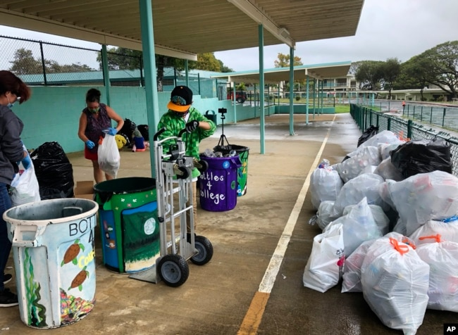 Genshu Price, kanan, dan relawan lainnya di S.W. King Intermediate School di Kāne'ohe, Hawaii, menyortir kaleng dan botol untuk Bottles4College. (Foto: AP)