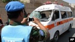 一位联合国观察员6月14日在大马士革郊外给一辆因炸弹袭击受损的救护车拍照