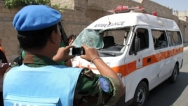 A UN observer photographs an ambulance that was destroyed after a car bomb exploded near the shrine of Sayyida Zeinab, in a suburb of Damascus, Syria, June 14, 2012.
