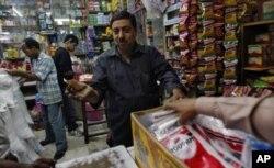 在印度首都德里市中部一个名为格罗尔巴格的地区,一个家庭商店的店主和顾客讨价还价(2011年11月24日)