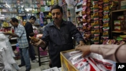 Ashwani Dang, owner of a mom and pop store, bargains with a customer at Karol Bagh market in New Delhi, India, November 24, 2011.