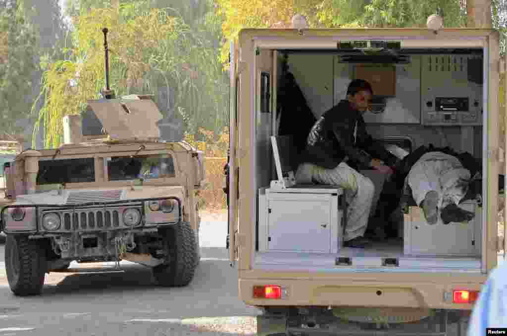 A soldier places the body of a civilian in an ambulance after Taliban insurgents attacked a bank in Helmand province, Dec. 17, 2014.